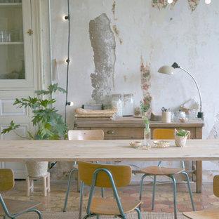 Cette image montre une salle à manger ouverte sur le salon style shabby chic de taille moyenne avec un mur multicolore et un sol en carreau de terre cuite.