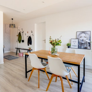 Example of a danish laminate floor and gray floor dining room design in Lyon with white walls