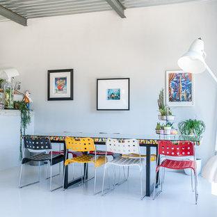 Réalisation d'une salle à manger ouverte sur le salon urbaine avec un mur blanc et un sol blanc.