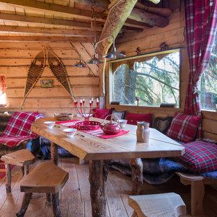 Idée de décoration pour une salle à manger chalet fermée et de taille moyenne avec un sol en bois brun, un mur marron et aucune cheminée.