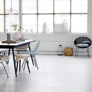 Réalisation d'une grande salle à manger ouverte sur le salon bohème avec un mur blanc et un sol en bois peint.
