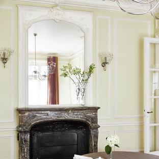Exemple d'une salle à manger chic fermée et de taille moyenne avec un sol en bois brun, une cheminée standard, un mur jaune et un manteau de cheminée en pierre.