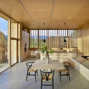 Réalisation d'une salle à manger ouverte sur le salon design de taille moyenne avec un mur beige et béton au sol.
