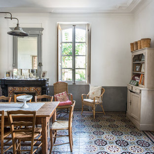 Example of a farmhouse ceramic tile dining room design in Montpellier with white walls, a standard fireplace and a tile fireplace