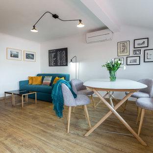 Cette photo montre une salle à manger ouverte sur le salon tendance de taille moyenne avec un mur blanc, un sol en bois brun et aucune cheminée.