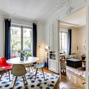 Cette image montre une grand salle à manger ouverte sur le salon traditionnelle avec un mur blanc, un sol en bois brun et aucune cheminée.