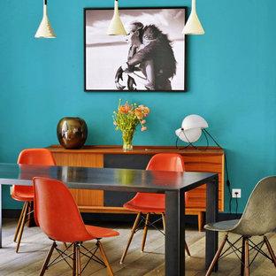 Inspiration pour une salle à manger bohème fermée et de taille moyenne avec un mur bleu, un sol en bois brun et aucune cheminée.