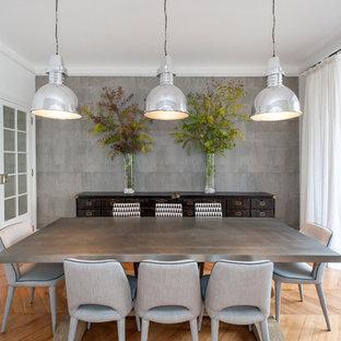 Cette photo montre une salle à manger chic fermée avec un mur gris, un sol en bois clair et un sol beige.