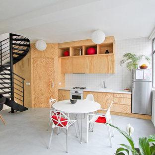 Exemple d'une salle à manger ouverte sur la cuisine éclectique de taille moyenne avec un mur blanc, béton au sol et aucune cheminée.