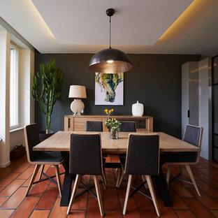 Cette photo montre une salle à manger tendance avec un mur gris et un sol orange.