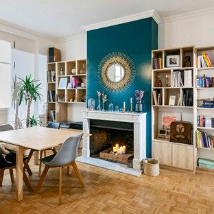Inspiration pour une salle à manger design avec un mur blanc, un sol en bois brun, une cheminée standard et un sol marron.