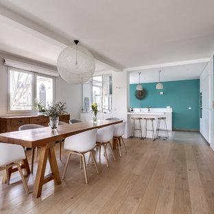 Exemple d'une salle à manger ouverte sur la cuisine tendance avec un mur blanc, un sol en bois clair et un sol beige.