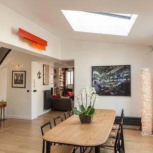 Exemple d'une salle à manger ouverte sur le salon tendance de taille moyenne avec un mur blanc et un sol en bois clair.