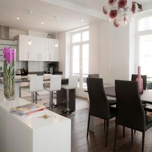 Cette image montre une salle à manger ouverte sur le salon design de taille moyenne avec un mur blanc, un sol en bois brun et aucune cheminée.