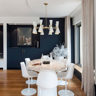 Modern inredning av en stor matplats med öppen planlösning, med blå väggar, ljust trägolv, en hängande öppen spis, en spiselkrans i gips och beiget golv