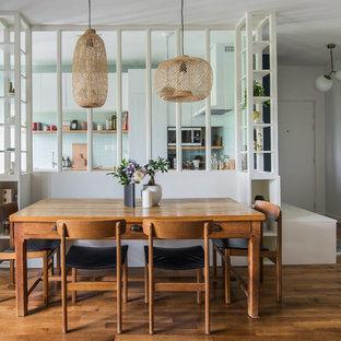 Cette photo montre une salle à manger ouverte sur la cuisine tendance de taille moyenne avec un mur blanc, un sol en bois brun et un sol marron.