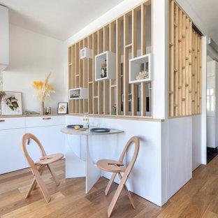 Idée de décoration pour une salle à manger ouverte sur le salon design avec un sol en contreplaqué.