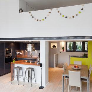 Exemple d'une grande salle à manger ouverte sur le salon tendance avec un mur jaune, un sol en bois clair et aucune cheminée.