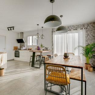 Exemple d'une grand salle à manger ouverte sur le salon tendance avec un sol gris et un mur blanc.