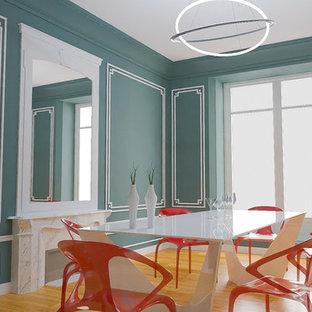 Aménagement d'une grande salle à manger classique fermée avec un mur bleu, un sol en bois clair, une cheminée standard, un manteau de cheminée en pierre et un sol marron.