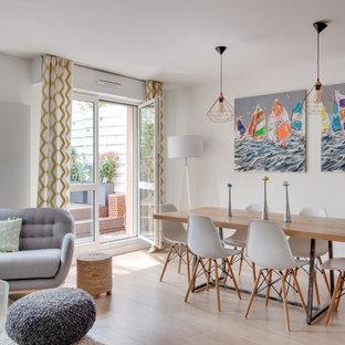 Aménagement d'une salle à manger ouverte sur le salon contemporaine avec un mur blanc et un sol beige.