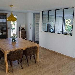 Cette photo montre une grande salle à manger ouverte sur la cuisine industrielle avec un mur blanc, un sol en bois clair et un sol beige.
