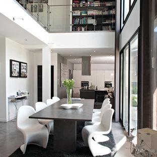 Cette photo montre une salle à manger ouverte sur le salon tendance avec un mur blanc et béton au sol.