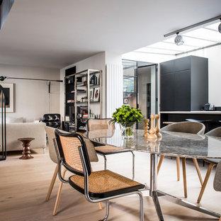 Réalisation d'une salle à manger design avec un mur blanc, un sol en bois clair et un sol beige.