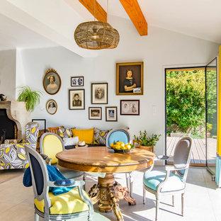 Aménagement d'une grande salle à manger ouverte sur le salon éclectique avec un mur bleu, un sol en carrelage de céramique, une cheminée standard, un manteau de cheminée en plâtre et un sol gris.