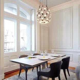 Idée de décoration pour une grand salle à manger ouverte sur le salon design avec un mur blanc, un sol en bois brun, un sol marron et boiseries.
