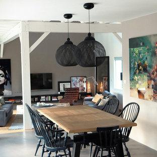 Idées déco pour une salle à manger ouverte sur le salon contemporaine de taille moyenne avec un mur blanc, béton au sol et aucune cheminée.