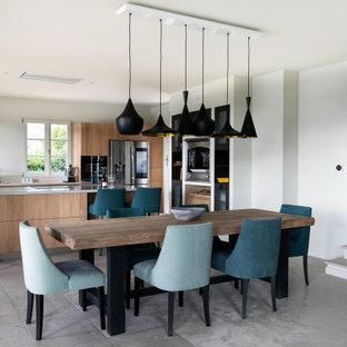 Cette photo montre une grande salle à manger ouverte sur la cuisine tendance avec un mur blanc et un sol gris.