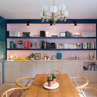 Idée de décoration pour une petit salle à manger ouverte sur le salon design avec un sol en bois clair, un mur multicolore et aucune cheminée.