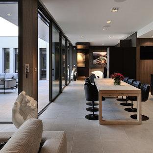 Aménagement d'une très grand salle à manger ouverte sur le salon contemporaine avec un mur marron.