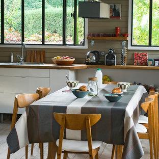 Aménagement d'une salle à manger ouverte sur la cuisine campagne de taille moyenne avec un mur gris, un sol en bois clair et aucune cheminée.