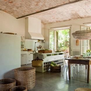 Idee per una grande sala da pranzo aperta verso la cucina country con pareti bianche, pavimento in cemento e nessun camino