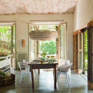 Cette photo montre une grand salle à manger ouverte sur la cuisine nature avec un mur beige et béton au sol.