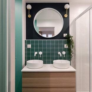 Idée de décoration pour une douche en alcôve principale design de taille moyenne avec des portes de placard en bois clair, un carrelage vert, des carreaux de céramique, un mur vert, un sol en carrelage de céramique, une vasque, un plan de toilette en stratifié, un sol vert, un plan de toilette blanc, meuble double vasque, meuble-lavabo suspendu, un placard à porte plane et une cabine de douche à porte coulissante.