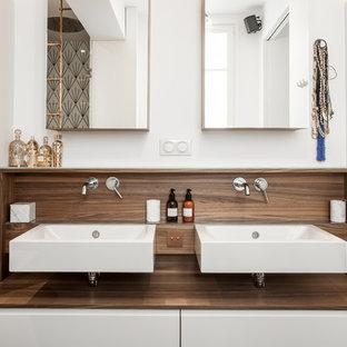 Cette image montre une salle de bain design avec un placard à porte plane, des portes de placard blanches, un mur blanc et un lavabo suspendu.