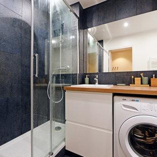 Cette photo montre une salle de bain tendance de taille moyenne avec un placard à porte plane, des portes de placard blanches, un carrelage bleu, un lavabo posé, un plan de toilette en bois, un sol bleu, une cabine de douche à porte battante, un plan de toilette marron, meuble simple vasque et meuble-lavabo encastré.