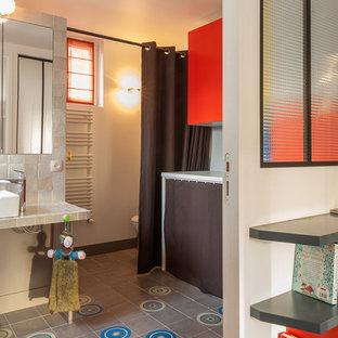 Immagine di una stanza da bagno per bambini design di medie dimensioni con ante a filo, ante arancioni, vasca sottopiano, doccia a filo pavimento, WC sospeso, piastrelle grigie, piastrelle in ceramica, pareti bianche, pavimento in cementine, lavabo da incasso e top piastrellato
