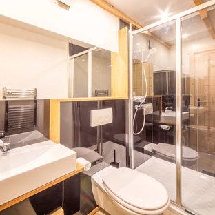 Idee per una stanza da bagno con doccia stile rurale di medie dimensioni con doccia alcova, WC sospeso, piastrelle nere, piastrelle a specchio, pareti nere, pavimento con piastrelle in ceramica, lavabo sospeso, top in laminato e pavimento beige