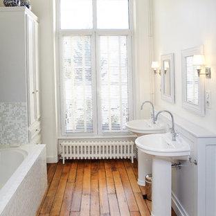 Exemple d'une salle de bain principale chic de taille moyenne avec un lavabo de ferme, carrelage en mosaïque, un mur blanc, un sol en bois brun, des portes de placard blanches, une baignoire posée, un carrelage beige et un carrelage gris.