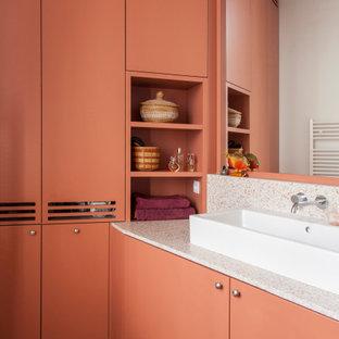 Inspiration pour une salle de bain design avec un placard à porte plane, des portes de placard oranges, un mur orange, une vasque, un sol beige et un plan de toilette blanc.