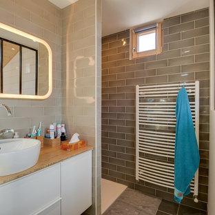 Exemple d'une très grand salle de bain scandinave avec un placard à porte plane, des portes de placard blanches, un espace douche bain, un carrelage beige, un mur beige, une vasque, un plan de toilette en bois, aucune cabine et un plan de toilette marron.