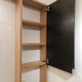 Esempio di una piccola stanza da bagno padronale design con ante nere, vasca sottopiano, vasca/doccia, piastrelle bianche, pareti bianche, pavimento in linoleum, lavabo sottopiano, top in legno, pavimento beige e porta doccia a battente