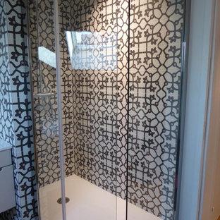 Foto di una stanza da bagno con doccia contemporanea di medie dimensioni con ante di vetro, ante bianche, doccia aperta, WC sospeso, piastrelle nere, piastrelle in ceramica, pareti rosa, pavimento con piastrelle in ceramica, lavabo rettangolare e top in superficie solida