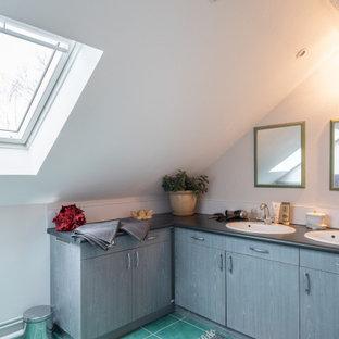 Réalisation d'une salle d'eau design de taille moyenne avec un placard à porte plane, des portes de placard en bois brun, un mur blanc, un lavabo posé, un sol vert, un plan de toilette noir, meuble double vasque et meuble-lavabo encastré.