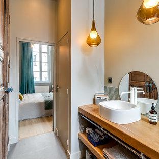 Réalisation d'une salle de bain principale nordique de taille moyenne avec un placard sans porte, des portes de placard en bois brun, un carrelage vert, carrelage en mosaïque, un mur beige, un sol en carrelage de céramique, une vasque, un plan de toilette en bois et un plan de toilette marron.