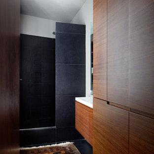 Immagine di una piccola stanza da bagno con doccia design con ante in legno bruno, piastrelle nere, doccia alcova, pareti bianche e lavabo sottopiano